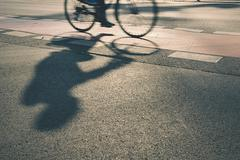 Silhouette of cyclist on the street at sunrise Stock Photos
