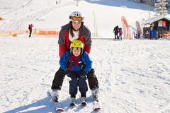 Stock Photo of Beautiful young mom and her toddler boy, skiing in the mountains, winter time