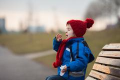 Little boy, sneezing and blowing his nose outdoor on a sunny winter day Stock Photos