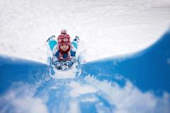 Cute little boy, going down a snowy slide Stock Photos