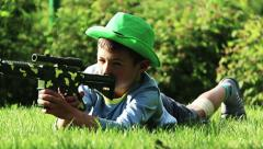 boy with a toy gun lying on the grass, takes aim - stock footage
