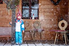 Adorable little boy with lantern, standing in front of a winter cottage while - stock photo