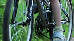 boy rides a bicycle in nature, close-up pedals and wheels - stock footage