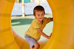 Stock Photo of Cute little boy, playing in a rolling plastic cylinder ring, full with air