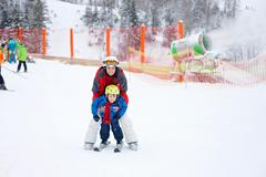 Beautiful young mom and her toddler boy, skiing in the mountains, winter time Stock Photos