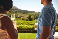 Couple at winery with glass of white wine - stock photo