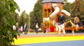 Children and parents having fun on playground in park, slow motion. Footage