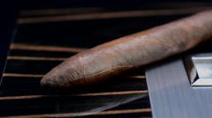 Cuban cigar laying on an elegant wooden humidor Stock Footage