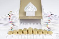 Step of gold coins with house on envelope between paperwork - stock photo