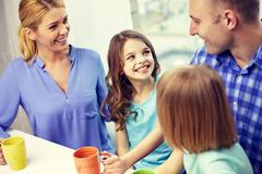Happy family drinking tea with cups at home Stock Photos