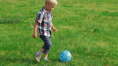 Elementary aged boy kicking ball in the field Stock Footage