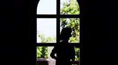 silhouette of a boy stands near a window and waving hand - stock footage