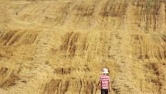 Boy is in a yellow field, boy is in the straw, boy go on mown field Stock Footage