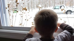 Little boy looks out his window to find a winter wonderland Stock Footage