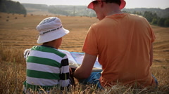 Father and son reading a book on top of a mountain in the field, a great review Arkistovideo