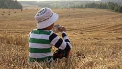 Boy drinks from a glass in a field on top of the mountain, a great review Stock Footage