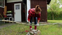 Woman struggling of cutting a wood with hand saw - stock footage
