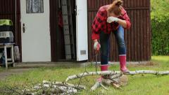 Tired woman cutting wood with hand saw Stock Footage
