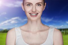 Happy beautiful girl with braces - stock photo
