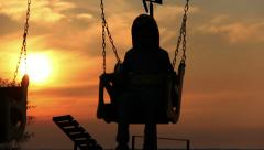 Boy on a swing at sunrise a boy on a swing at sunset, silhouette, river Stock Footage