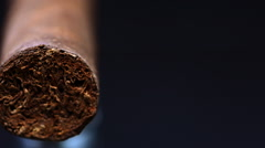 Handrolled cuban cigar on cigar lighter isolated on black background Stock Footage