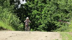 Boy pulls the bike up the hill, then sits down and goes on the road Stock Footage