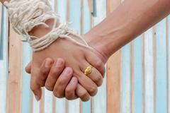bride and groom hold one's hands with color wooden background - stock photo