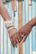 Bride and groom hold one's hands with color wooden background Stock Photos