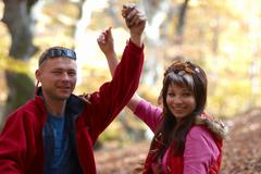 Stock Photo of Young couple enjoying the falling leaves