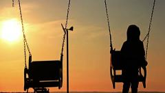 Boy on a swing at sunset a boy on a swing at sunrice, silhouette, river Stock Footage