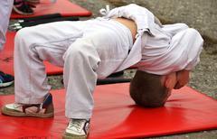 Young judo athlete makes a bridge in a white kimono with a red carpet Stock Photos