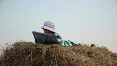 boy on haystack opens the book and starts read, boy reading a book in the manger - stock footage