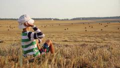Boy sitting and throwing stones, a boy on a hill in the throws stones Stock Footage