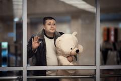 Man holding toy bear and looking sadly into the distance. Stock Photos