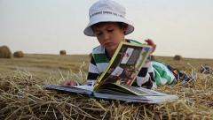 boy thumbs through the book on a haystack, a boy reading a book in the manger - stock footage