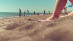 Close up of woman leg on the beach and blurred people on background - stock footage