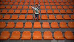Boy sitting at the stadium and glad his team scored a goal. boy watching match Stock Footage