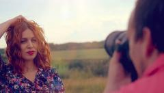 Young photographer takes photo of young red-haired woman at summer outdoor on Stock Footage