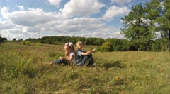 Stock Video Footage of Happy children laughing and talking in a meadow.