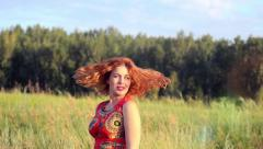 Young red-haired woman with full red lips posing to photographer at summer Stock Footage
