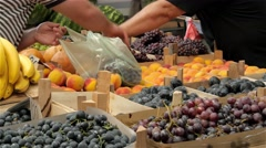 Grapes and other fruits on stall, buyer adds grapes seller to puts in bag. 4k Stock Footage