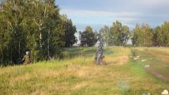 Two motorcyclists on bike going to the forest on road in field. Summer time Stock Footage