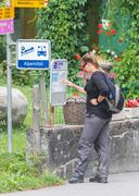 LENK, SWITZERLAND - JULY 23, 2015: Young woman checking the timetable at the  Kuvituskuvat