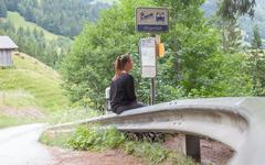 LENK, SWITZERLAND - JULY 23, 2015: Young woman checking the timetable at the  - stock photo