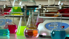 Colorful glasswares stand on table on two rotating  shakers background  close up Stock Footage