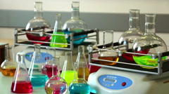 Colorful laboratory glasswares on shakers and table focus on front Stock Footage