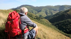 Hiker sitting on a rock admiring Basque Country scenery Stock Footage