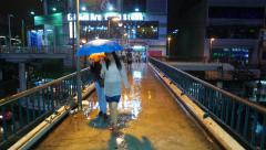 Strong rainfall at dark evening, woman with umbrella come towards on footbridge Stock Footage
