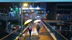 Two asian women with umbrella come towards and pass, heavy rain at night Stock Footage