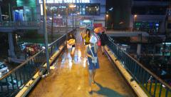 Woman run towards from rainfall over pedestrian bridge, urban night view Arkistovideo